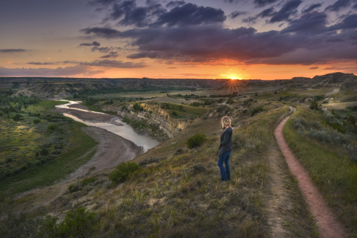 Woman hiking as the sun is setting at theodore roosevelt national park t20 3w7r13