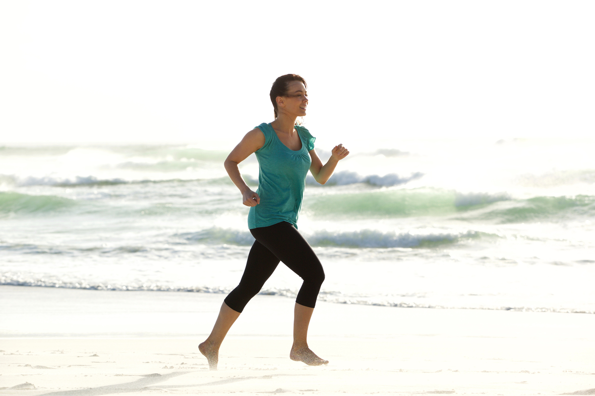 Attractive young woman running alone on the beach phxtjcg